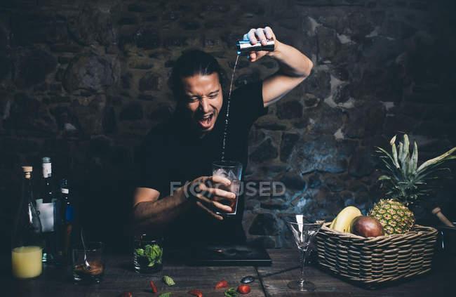 Мужчина наливает ингридиент в коктейльный бокал — стоковое фото