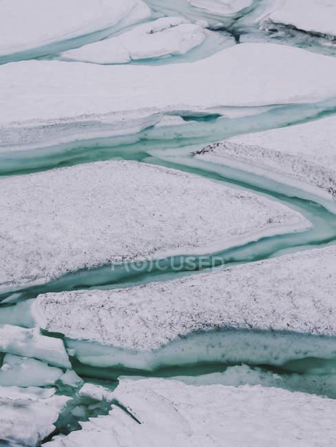 Rachaduras azuis em camadas de gelo coberto de neve — Fotografia de Stock