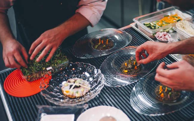 Mains de récolte prenant des ingrédients pour les plats à la cuisine du restaurant — Photo de stock