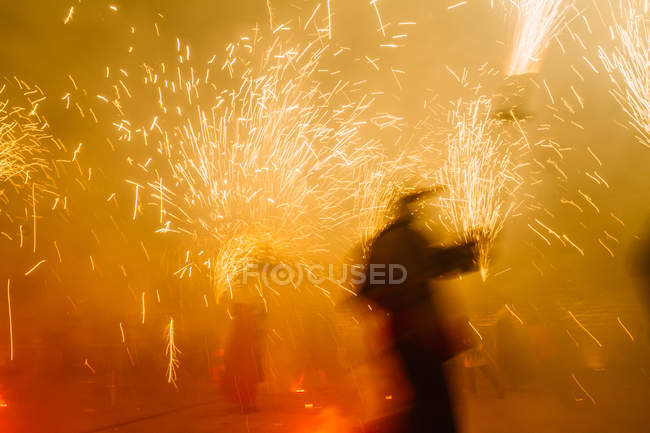Bright sparkling fireworks and blurred silhouette on night street celebration scene — Stock Photo