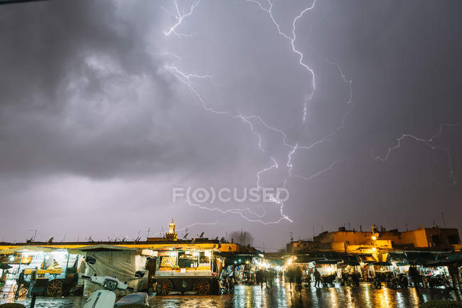 Night cityscape with stormy lightning in dark sky after rain. — Stock Photo