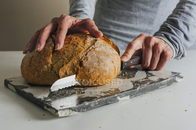 Woman cutting freshly baked bread on marble table — Stock Photo