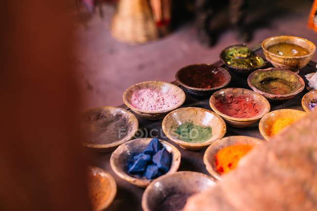 Kleine Keramikschalen mit hellem Puder in verschiedenen Farben auf dem Tisch. — Stockfoto