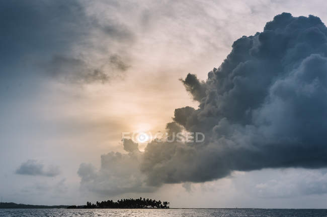 Fluffy storm cloud in colorful sky above sea surface. — Stock Photo