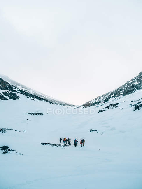 Distant view of group of tourists walking at snowy mountain meadow — Stock Photo