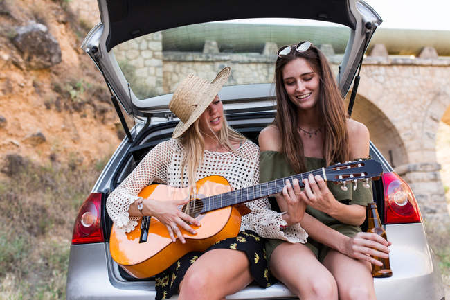 girls sitting with guitar in car trunk stock photo 171467346