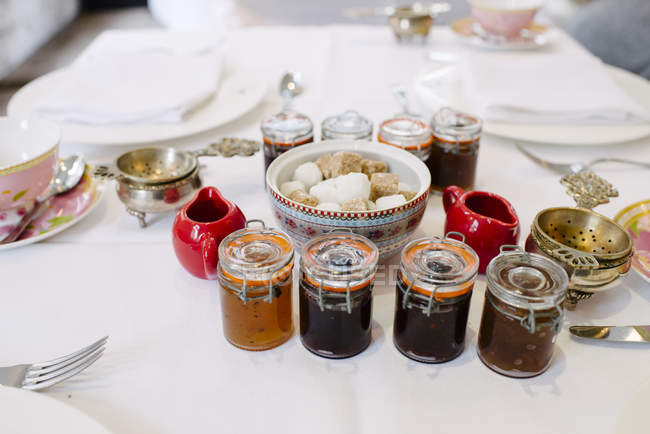 Close up view of different jams and sugar served on a table. — Stock Photo