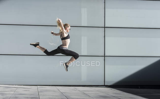Sportive woman in powerful jump — Stock Photo