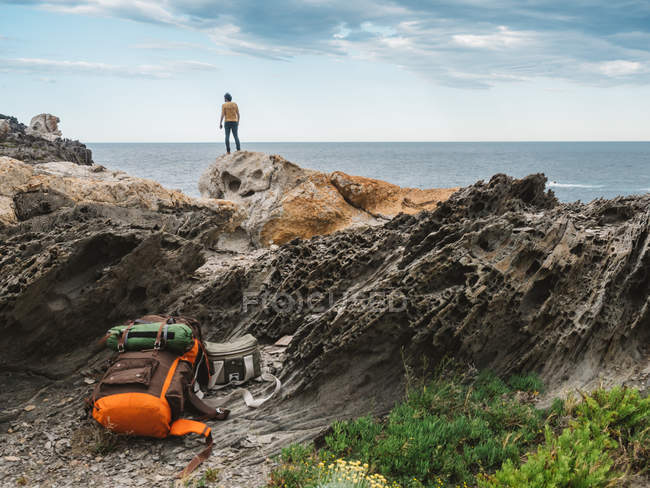 Travel backpack lying on rocks over traveler standing on rock cliffs and admiring oceanscape — Stock Photo