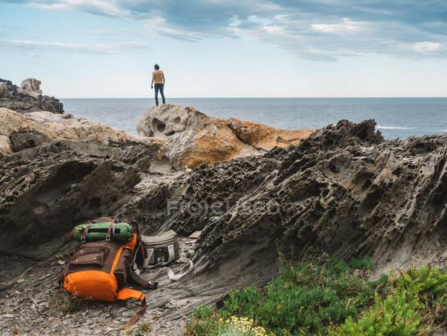 Voyage sac à dos, allongé sur les rochers au voyageur debout sur les falaises rocheuses et admirer la mer — Photo de stock