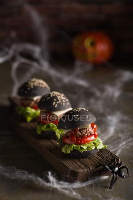 Ряд Хеллоуїн гамбургери на дерев'яну шахівницю — стокове фото