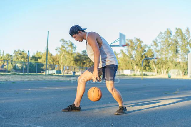 Young man dribbling basketballball — Stock Photo