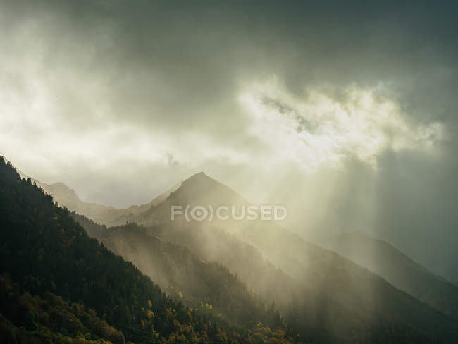Picturesque landscape of misty mountains range lighted with sun rays struggling through heavy clouds in gloomy sky. — Stock Photo