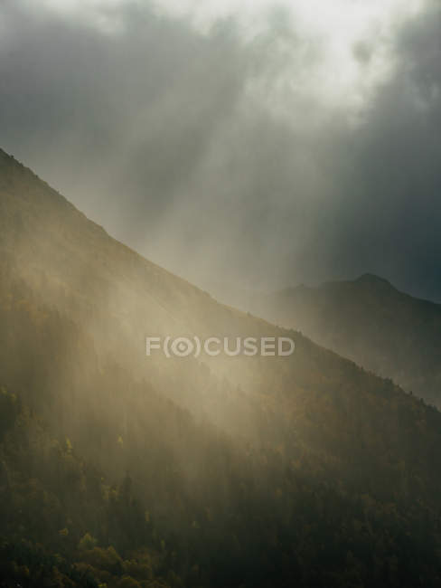 Picturesque view of sun rays penetrating clouds in gloomy sky above mountains range. — Stock Photo