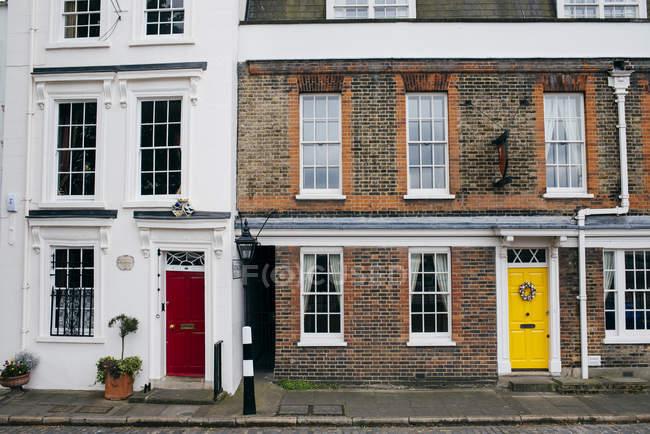 Vista exterior de casas fachadas con puertas de colores brillantes - foto de stock