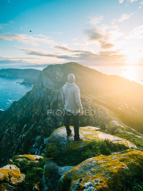 Vista posteriore dell'uomo in piedi sulla roccia muscosa sopra le montagne e l'oceano in piena luce del sole . — Foto stock
