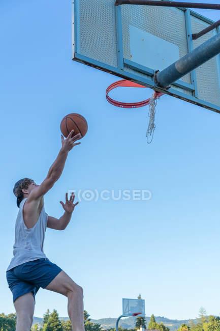 Мужчина бросает мяч на баскетбольном ринге — стоковое фото
