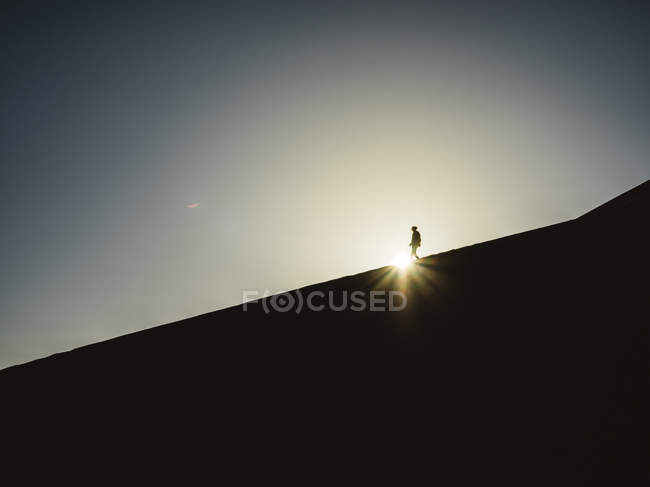 Anonymous person walking in desert — Stock Photo