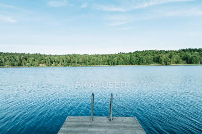 Píer de madeira e água azul do lago com floresta na costa . — Fotografia de Stock
