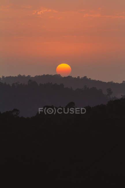 Vue idyllique sur le coucher de soleil orange sur la colline et la forêt . — Photo de stock