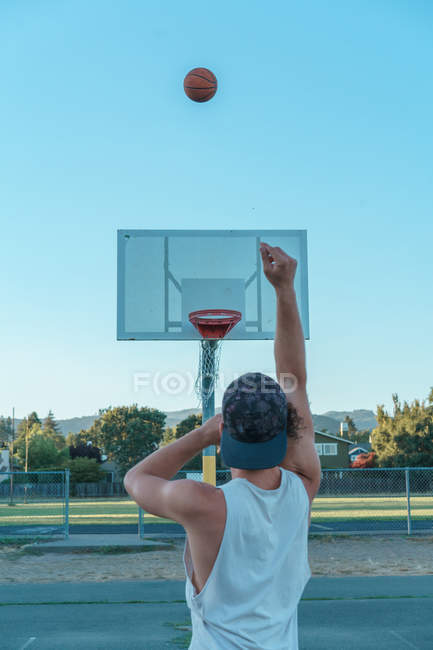 Man throwing basketball ball in ring — Stock Photo
