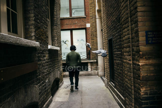 Anonymous dweller walking on paved narrow alley between old buildings. — Stock Photo
