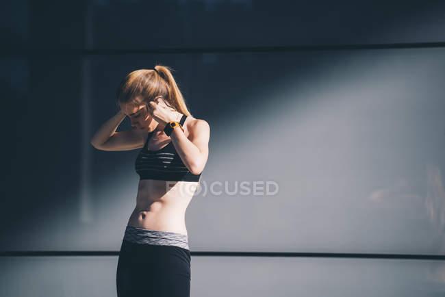 Sportswoman putting on earphones — Photo de stock