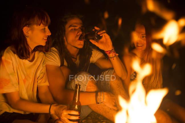 Freunde, trinken Bier am Lagerfeuer — Stockfoto