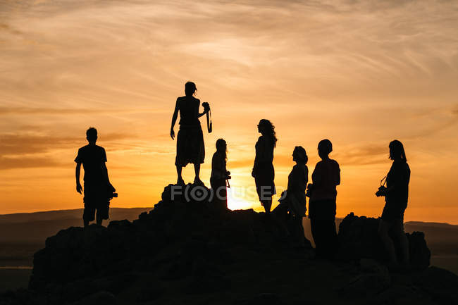 Силуэты людей на закате — стоковое фото