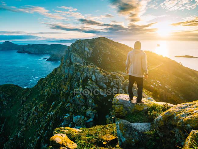 Vista posteriore dell'uomo in piedi sulla roccia sullo sfondo delle montagne e dell'oceano in piena luce del sole . — Foto stock