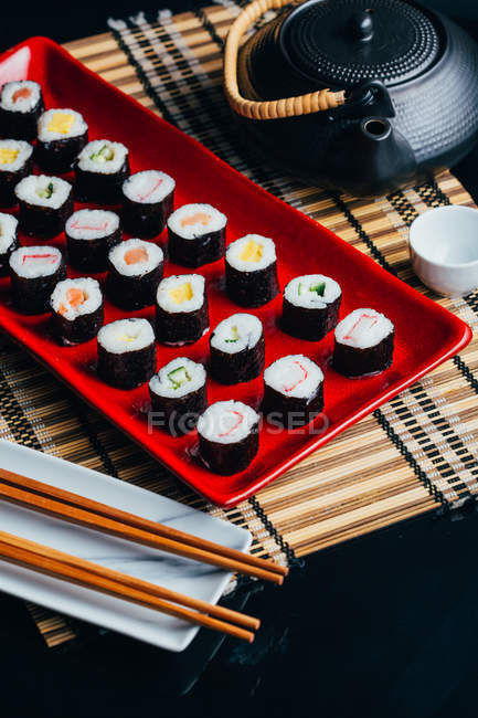 Served sushi set on red plate — Stock Photo