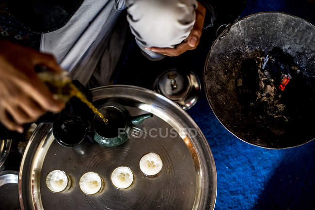 Hand pouring tea to small cups — Stock Photo