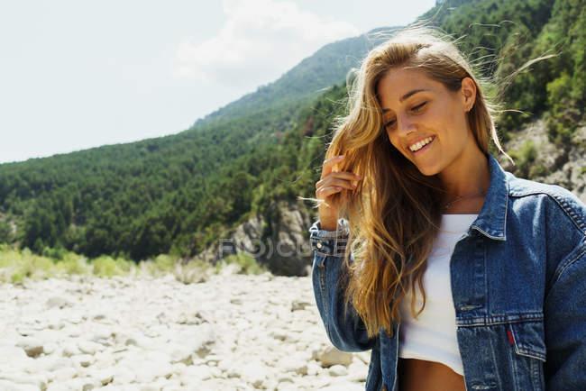 Heureuse femme qui pose sur paysage de montagnes — Photo de stock