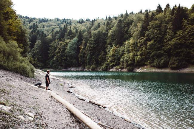 Vista laterale del Viandante uomo turistica in piedi al puntello del fiume nella foresta — Foto stock