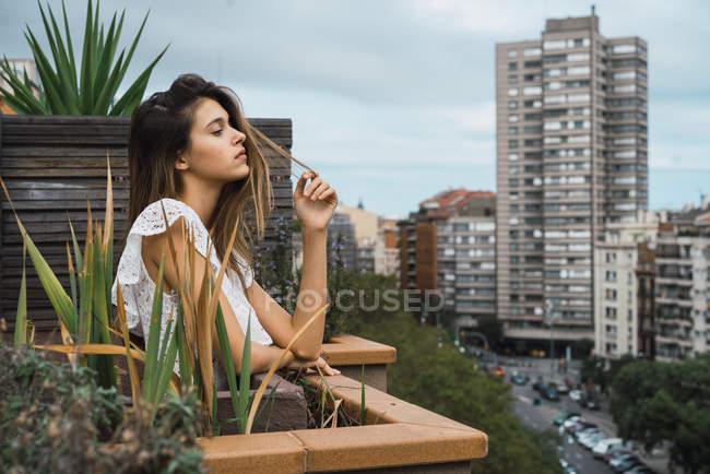 Sensuale donna in posa sul balcone con facciate edifici su sfondo — Foto stock