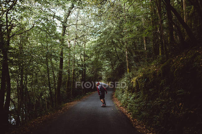 Rear view of man riding skateboard on asphalt road going through forest. — Stock Photo