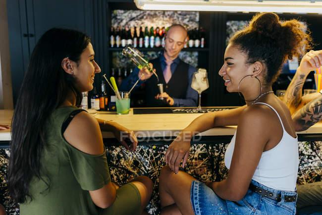 Donne sedute al bancone del bar mentre il barman prepara bevande — Foto stock