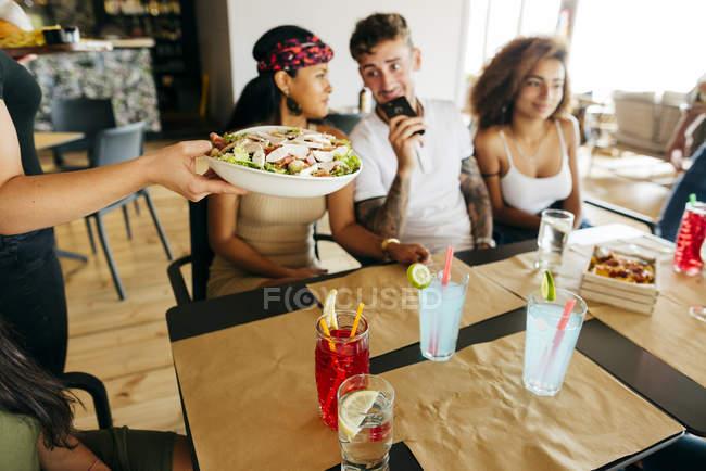 Урожай неузнаваемый официант, подающий салат для группы друзей за столиком кафе — стоковое фото