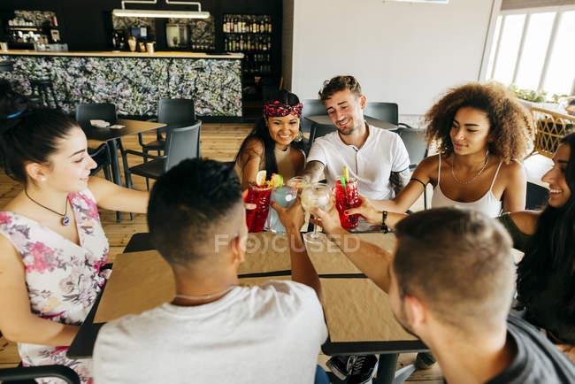 Amigos alegres sentados à mesa do café e brindando — Fotografia de Stock