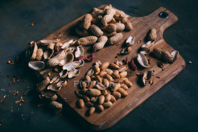Haufen geschälter Erdnüsse und Schalen auf einem Holzschneidebrett auf dunklem Hintergrund — Stockfoto