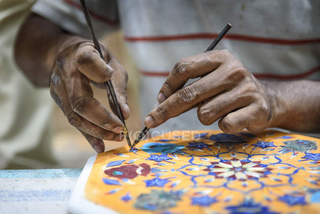 Close-up hand of person drawing on traditional Indian mandala — Stock Photo