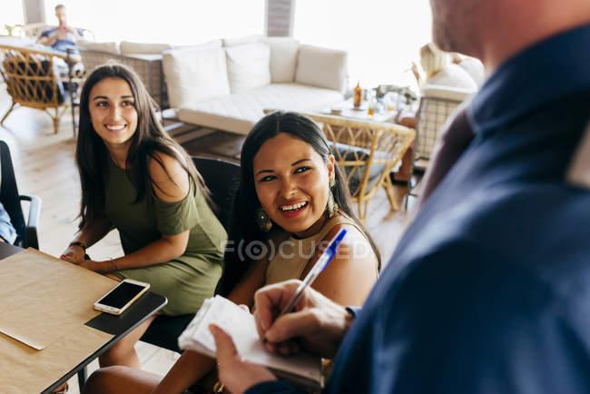 Gens joyeux assis dans le café et vous passez votre commande — Photo de stock