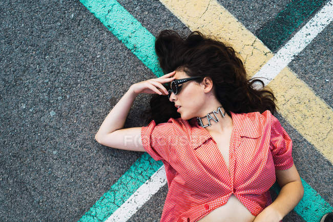 From above view of brunette woman in sunglasses lying on lines of asphalt road. — Stock Photo