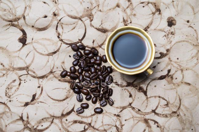 Кофейная кружка и зерно кофе на белой выветренной бумаге — стоковое фото