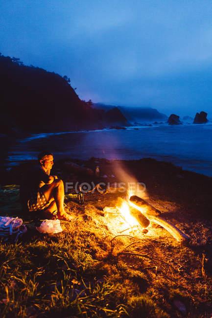 Homme en short assis à côté du feu de camp sur le bord de la mer la nuit et regardant le feu flamboyant . — Photo de stock