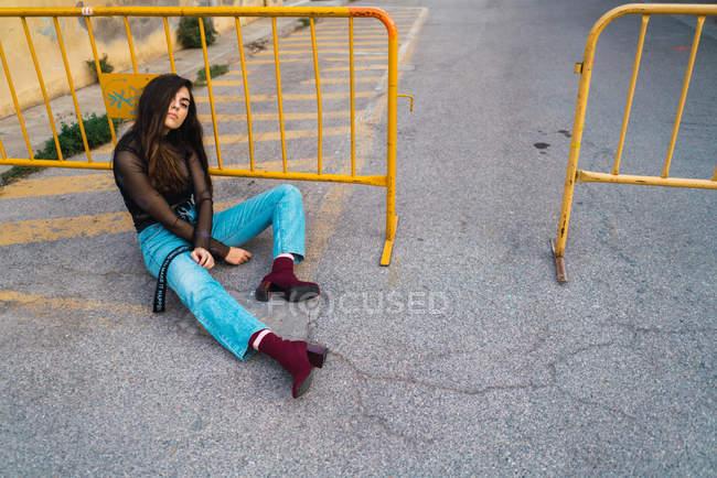 Brunette girl sitting on asphalt road beside yellow fence on city street. — Stock Photo