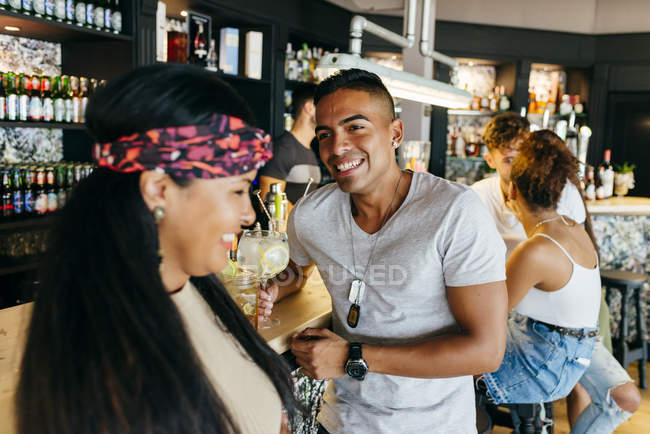 Cheerful friends drinking cocktails at bar counter — Stock Photo