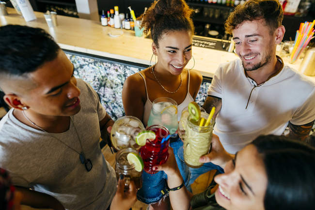 Cheerful friends clinking cocktails in bar — Stock Photo