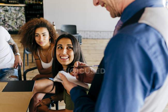 Chicas alegres pedido al camarero en la cafetería - foto de stock
