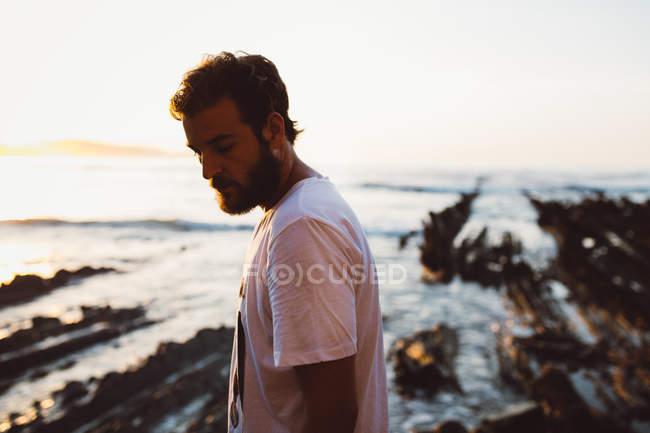Вид сбоку солнечного босоногого мужчины, позирующего на скале у берега — стоковое фото